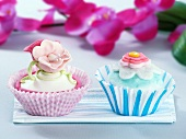 Two cupcakes decorated with sugar flowers