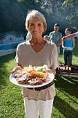 Three generation family standing beside barbecue grill in garden, focus on senior woman holding plate of food in foreground, smiling, portrait