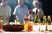 Family having barbecue in summer garden, focus on food and wine on table in foreground