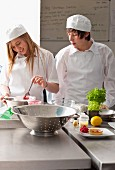 Trainee chefs working together in commercial kitchen
