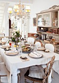 Set table in dining room with elegant period furniture, chandelier and dresser