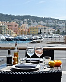 A table laid for two, with wine glasses, in a bistro on the harbour in Nice