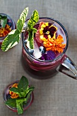 Blueberry Mint Tea Served in Jars and in a Pitcher with Edible Flowers and Mint Leaves; From Above