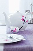 A teapot, a small milk jug and a plate, all with a flower motif