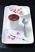 A porcelain platter with tiramisu in a cup and a dish of pralines