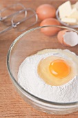 A raw egg on top of flour in a glass bowl, alongside eggs, butter and whisks