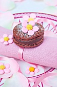Chocolate macaroon with sugar flowers on a pink napkin