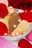 Vanilla and chocolate heart-shaped biscuits with sugar hearts and rose petals