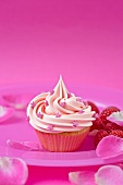 A pink strawberry cupcake with raspberries and rose petals