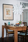 Modern dining table and traditional chairs below Bauhaus pendant lamp with fish scale shade in front of framed picture on wall