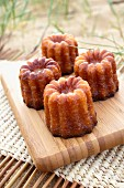 Four cannelés on a chopping board