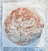 A loaf of bread on paper, on a marble slab, dusted with flour