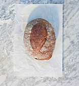 A loaf of bread on a piece of paper, on top of a marble surface dusted with flour