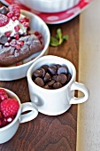 Mugs of Chocolate Chips and Raspberries with Chocolate Oatmeal Pudding Cake in Background