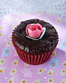 A chocolate cupcake with a sugar flower