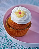A cupcake topped with icing and a decorative flower