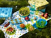 A picnic with a brightly coloured picnic blanket and floor cushions