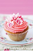 A cupcake decorated with pink frosting and sugar flowers