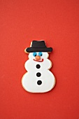 A snowman biscuit on a red surface