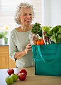 USA, New Jersey, Jersey City, Senior woman with grocery bag in kitchen