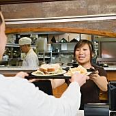 Customer receiving tray of food in bakery