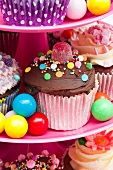Colorful cupcakes and candies for a party on a cake stand