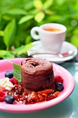 Chocolate souffle with summer berry sauce