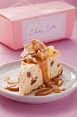 A piece of cheesecake with caramel sauce and sliced almonds