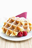 Waffles with icing sugar and raspberries