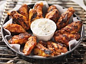 Barbecued chicken wings with dip in a tray on the barbecue