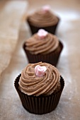 Three chocolate cupcakes with pink sugar flowers