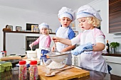 Germany, Girls and boy sifting flour in bowl