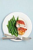 Chicken breast stuffed with blue cheese and wrapped in ham, served with green beans