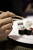 A hand reaching for a piece of sushi using chopsticks