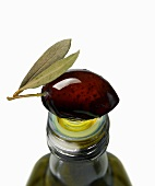 A black olive on top of an olive oil bottle