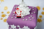 a model in icing of father Christmas holding up his arms on a purple and white Christmas cake with white stars and golden stars on a white background.