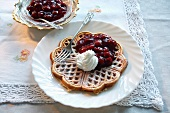 Waffles topped with cherry compote and cream