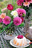 A table in the garden set with a Bundt cake, summer flowers and a hurricane lamp