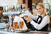 A waitress pouring draught beer in a pub