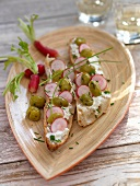 Slices of bread topped with olives and radish slices