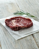 Raw beef steak with salt and rosemary on baking paper