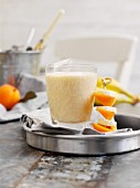 Apricot, banana and mandarin shake with a fruit skewer
