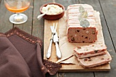 Meat terrine with raisins, wrapped in bacon, on a wooden board