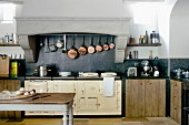 Antique kitchen table with chopping board on table in front of vintage range and collection of copper pans hung in masonry extractor