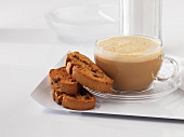 A cup of caffe latte with biscotti