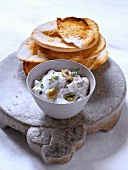 Creamy goat's milk yoghurt with thyme and olives, served with toasted bread