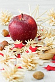 Christmas decorations with an apple, nuts and straw stars