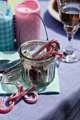 Candy canes, colourful candles and a drink on a table
