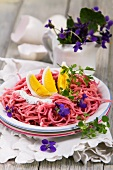 Beetroot pasta with a boiled egg, herb quark and violet flowers
