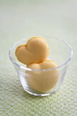 Heart-shaped peach macaroons in a small glass bowl